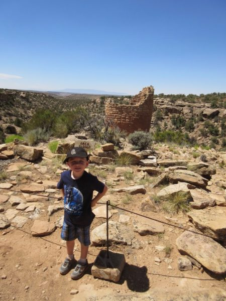 Young boy standing in front of Hovenweep ruin tower