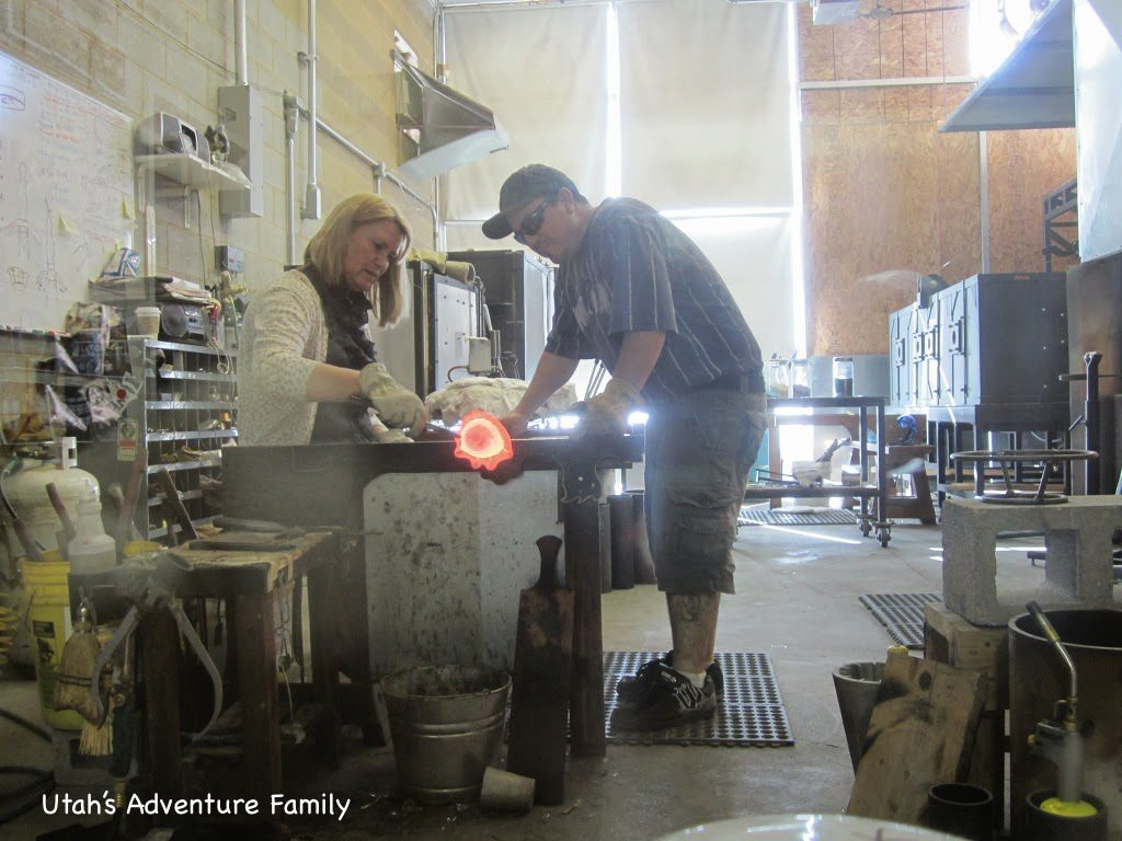 This lady is making a glass flower...she is pulling at the hot glass.