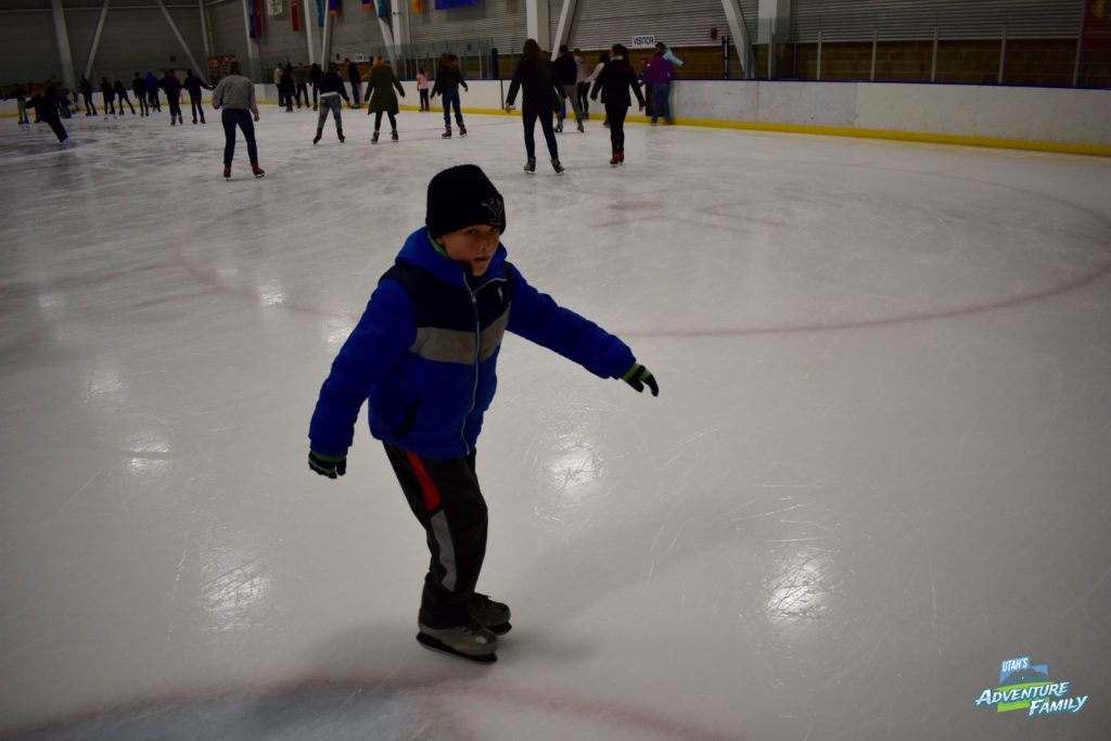 Boy ice skating at an indoor ice rink.