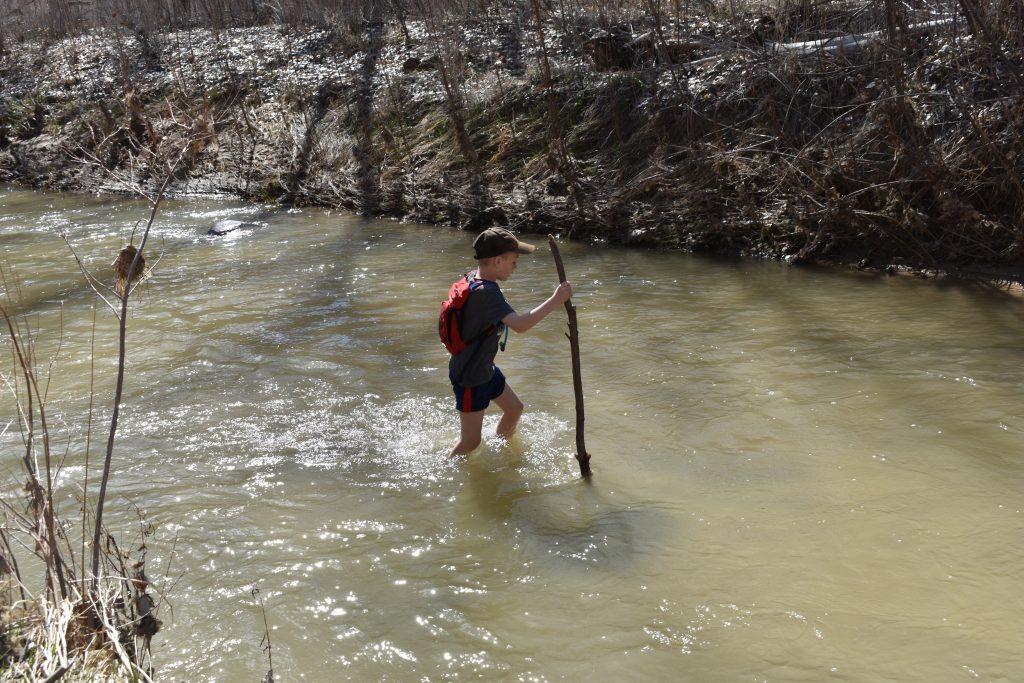 child crossing a river on the escalante natural bridge trail
