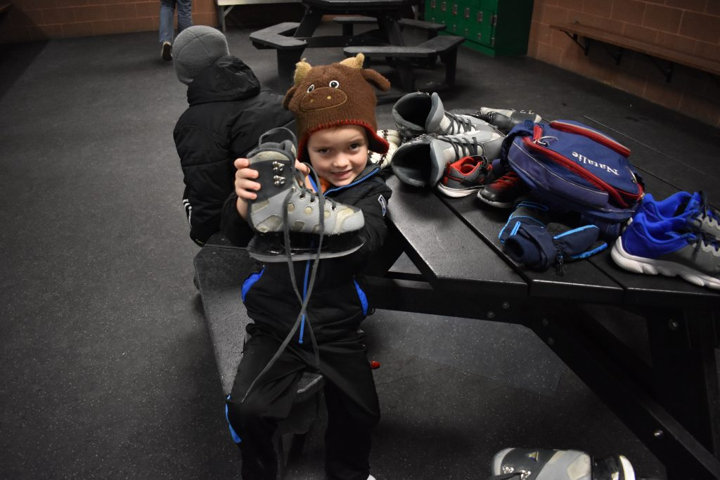 Child holding up ice skates by the rental desk.