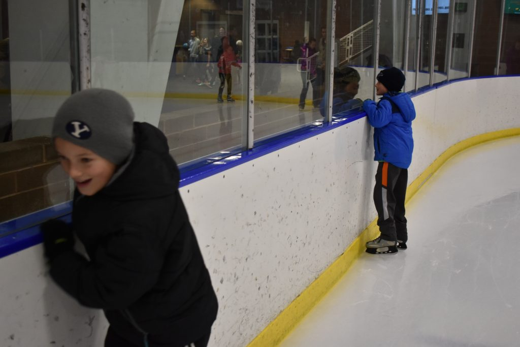 Two kids hanging on wall as they ice skate around the rink.
