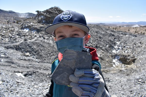 Child holding up a rock with a fossil impression at U Dig Fossils.
